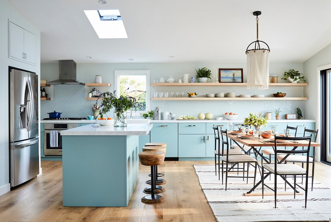 """With plenty of space for friends and family to hang out while Minnie cooks, the revamped kitchen is entertaining-central: """"It's so convivial,"""" Minnie says. Cheery blue lower cabinets combined with light-toned open shelving help the small space feel airy and open, while accents of dark metal in the chairs and the pendant light lend an edge to the seaside scheme. Sleek sink fittings and hardware by Waterworks help complete Minnie's ideal """"cook's kitchen."""""""