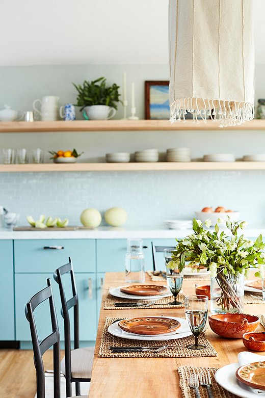Minnie's terracotta plates provide a warm contrast to the cool blue surroundings, while woven place mats and a fringed fabric light fixture add organic allure.
