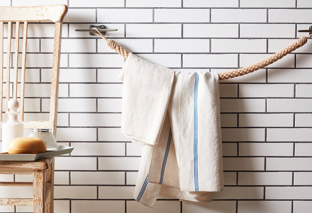 Looped around a set of boat cleats, a rope tieback becomes a nautical-chic towel bar.