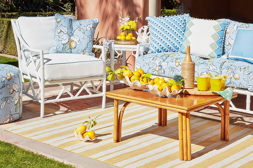 The Kit Sofa, Kit Lounge Chair, and Kit Round Pouf, all by Celerie Kemble for One Kings Lane, make up a chic and inviting outdoor seating area. The cheery lemon print is a dose of pure Palm Beach sunshine.