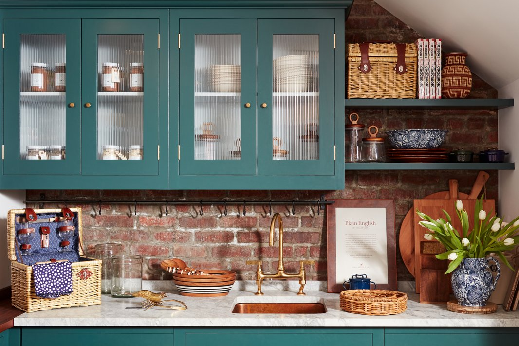 Wood accents and woven baskets fill the custom kitchen designed by cabinetmaker Plain English.