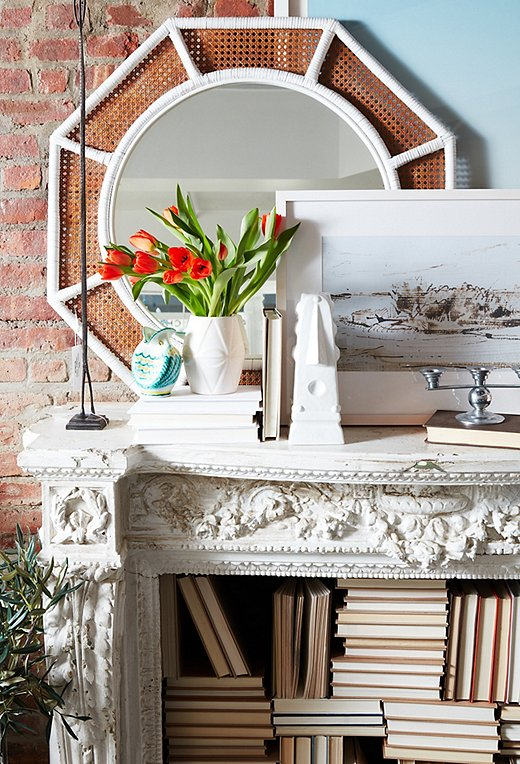 A caned mirror and a mix of sleek accents give the fireplace a warm, rich look.