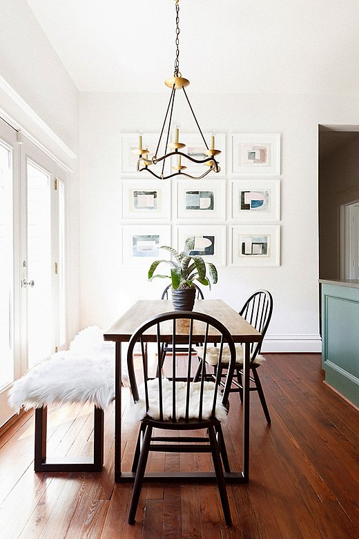 In the breakfast room, Elizabeth paired timeless Windsor chairs with a modern table (similar here) and bench, topped with a sheepskin for coziness. The Visual Comfort chandelier draws the eye up, emphasizing the high vaulted ceiling, while the artwork picks up on the color of the adjacent kitchen cabinets.