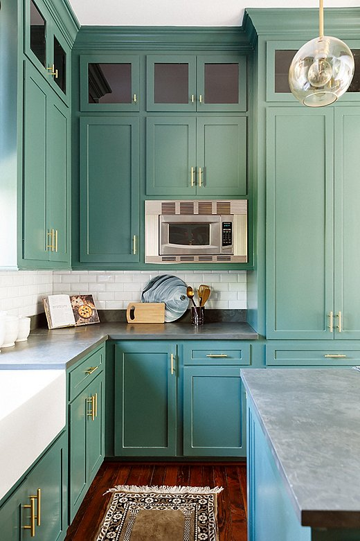 "The kitchen was small but got plenty of light, so Elizabeth suggested a daring dark-green paint color. ""I loved that my clients took some color risks and stepped outside the box,"" says Elizabeth. ""It was so fun seeing the kitchen transform."""