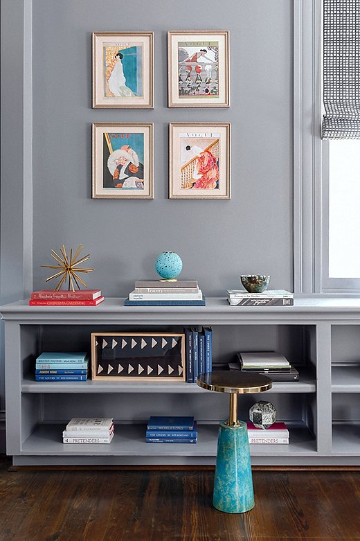 Stacks of books give the shelves a cool color-block effect. The framed illustrations above are in keeping with the home's vintage-meets-modern vibe.