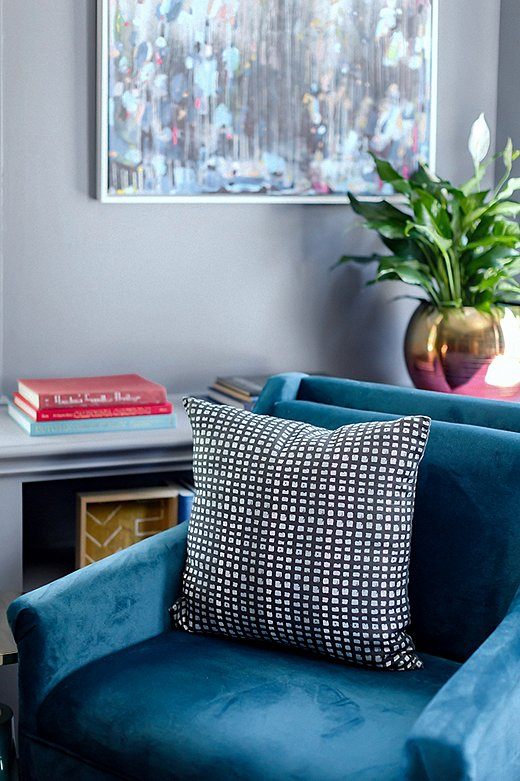 A pillow in Stone Textile Studio's Color Grid Print fabric tops a teal-velvet accent chair found on One Kings Lane.