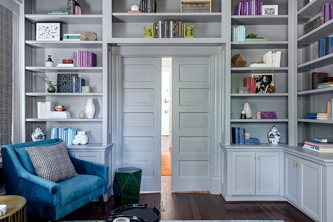 """My clients loved the charm in here,"" says Elizabeth of the library, which is right off the home's foyer. ""It is the first thing you see when you walk in, so we wanted this room to pop."" She painted both the entry and the library a lush gray, carrying the color onto the bookshelves, doors, and moldings to create an enveloping feel. Blue and purple accents complement the paint's cool undertones."