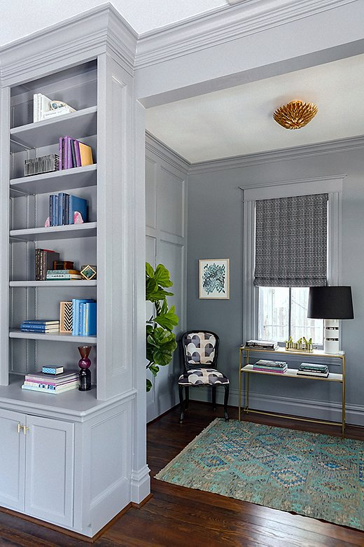 "The Roman shades in the entryway and library are also in Elizabeth's Color Grid Print fabric. ""I love how they pop against the wall color,"" she says. ""We wanted the textiles to be rich and had fun with mixing textures."" A kilim rug adds even more pattern, and a gold flush-mount fixture lends a touch of glamour."