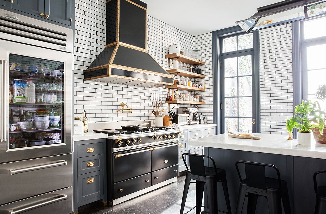A black Lacanche stove is a clear centerpiece of the kitchen. The walls are covered in a bricklike subway tile, framed by dark grout.