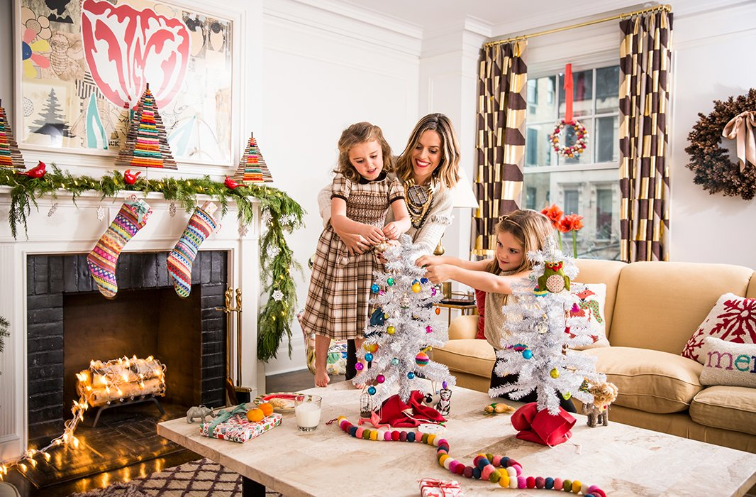 """Holiday decorating with the girls is so much fun,"" says Lilly, here seen helping Daisy and Grace with the top of a tree. (And note the surprising and fun use of electric lights in the fireplace.)"