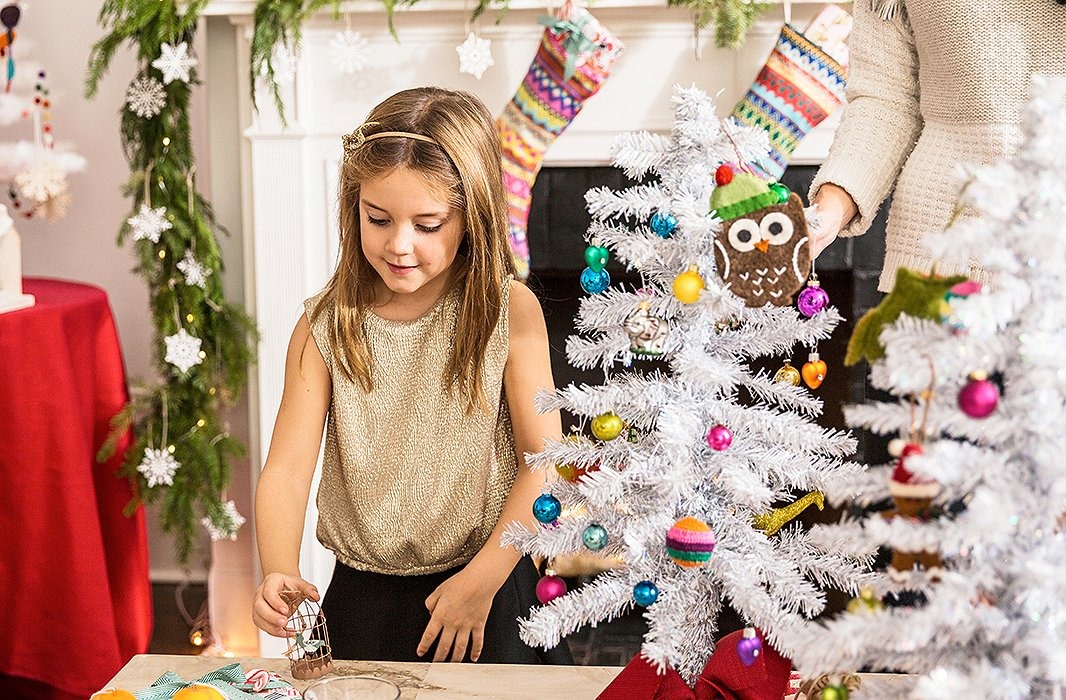 In front of the fireplace, which is dressed up with garland and glitzed up with silver ornaments, Grace prepares to place a birdcage ornament.
