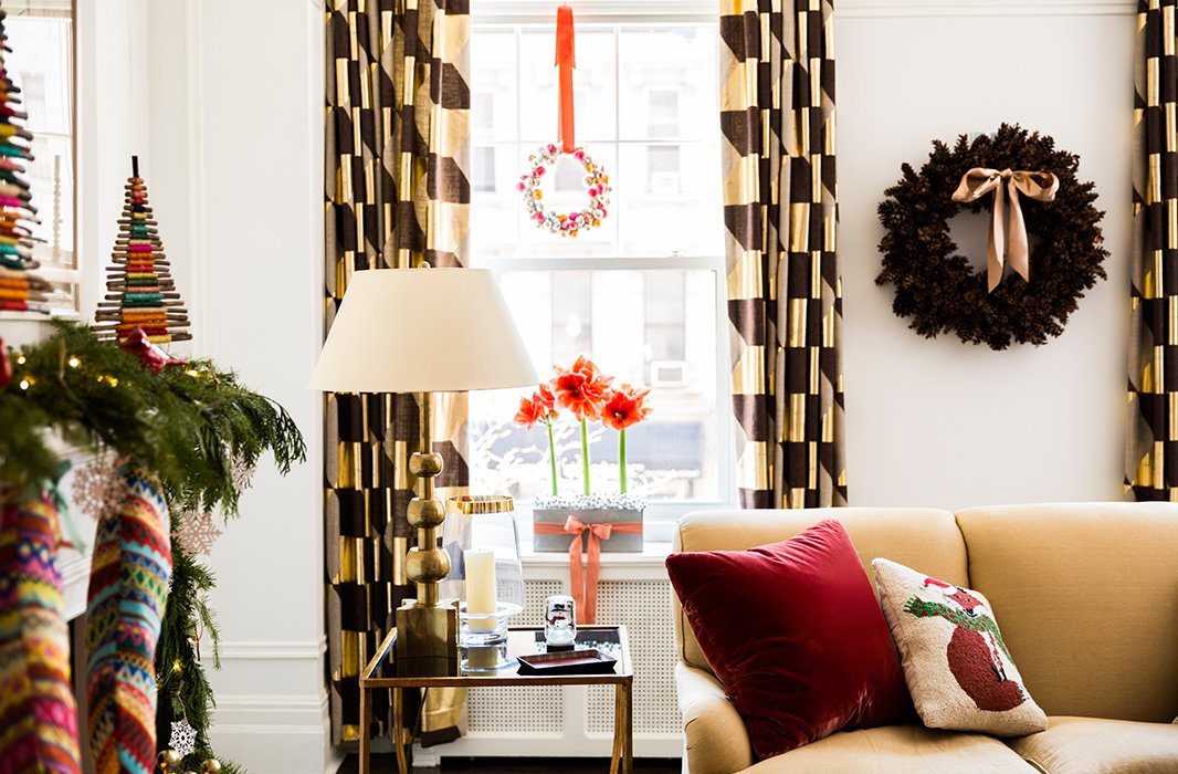 Sophisticated elements, like perfectly potted amaryllises and a pinecone wreath, mixed with a playful holiday pillow create the perfect balance.