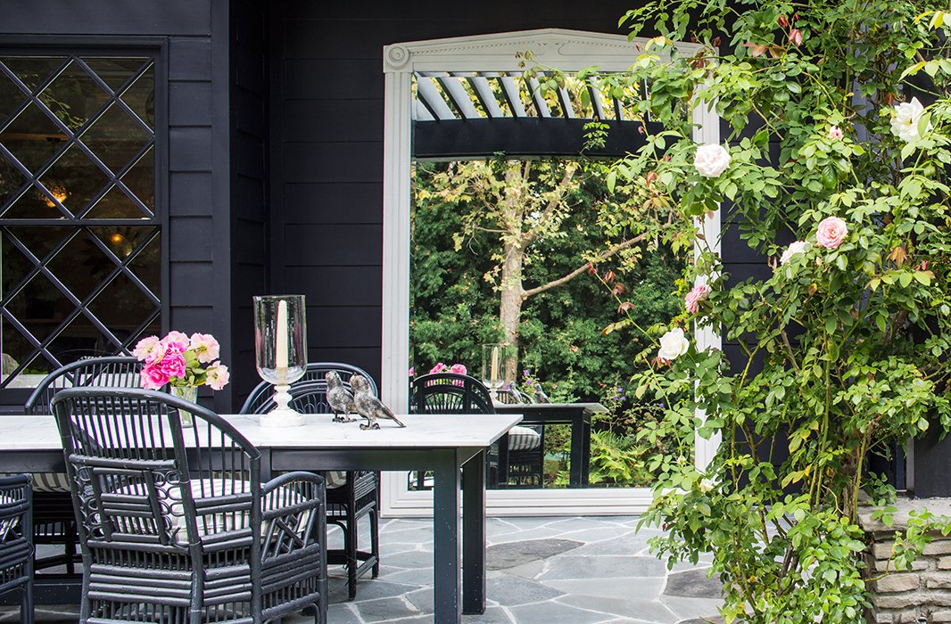 An oversize mirror dresses up the outdoor dining space of designer Windsor Smith's L.A. abode.