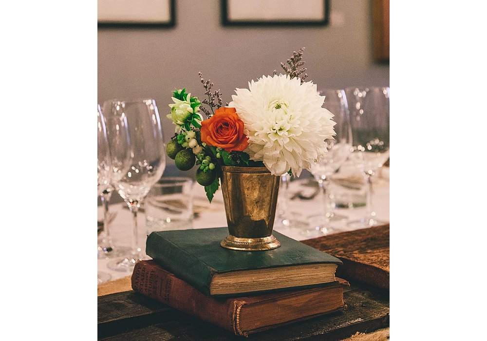 A brass mint julep cup serves as a vase for orange roses, white dahlias, and autumn greenery. The books, all flea-market finds, include a vintage copy of Dickens' Tale of Two Cities.