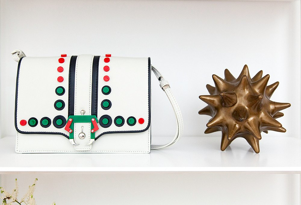 A sweet Paula Cademartori bag shares shelf space with a spiny accessory by DwellStudio.