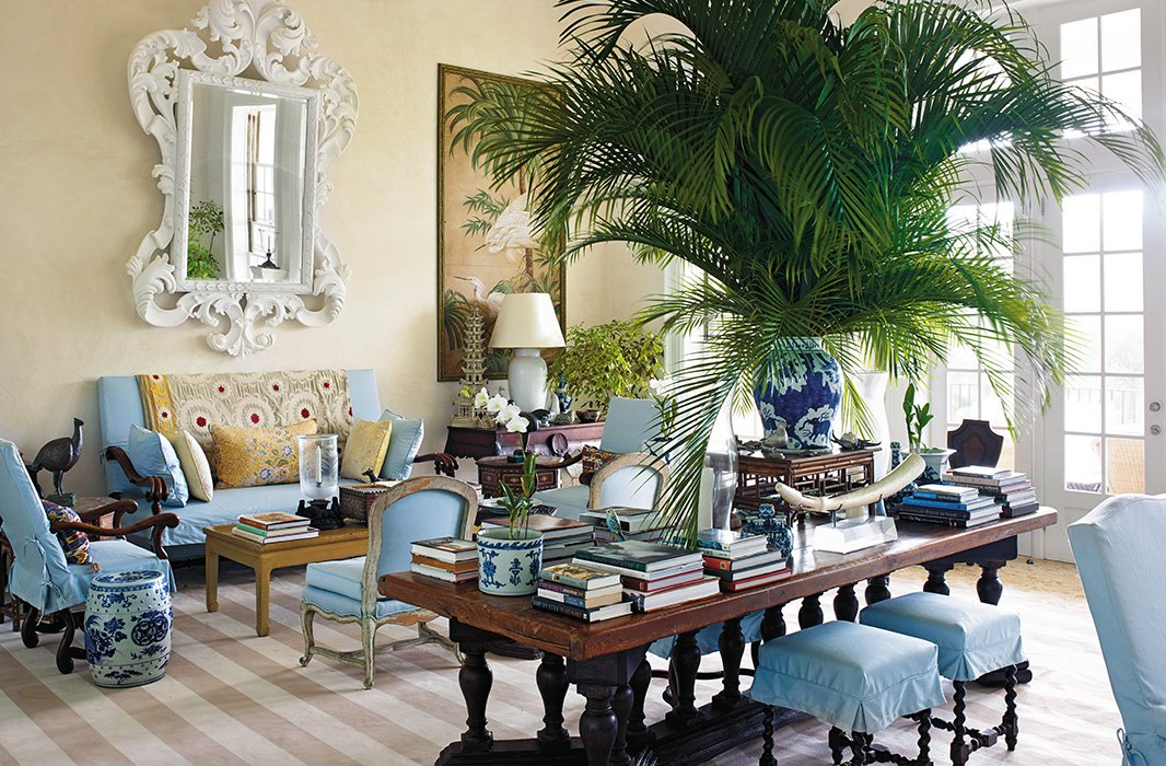 """If you have formal furniture and decide you would like a more tropical look for it, try covering the pieces in inexpensive cotton canvas or duck,"" writes Bunny, pointing out the sky-blue slipcovers she used to ease up the sofas and chairs in the high-ceilinged island living room."
