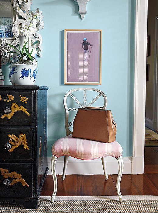 A vanity chair in a guest bedroom functions as both a beautiful perch and a holding spot for bags and coats. Its chipped white-painted frame recalls a gesture favored by famed decorator Dorothy Draper.