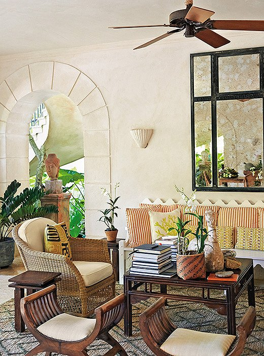 """Rooms become relaxed when there is a little patina on the furniture and textiles are mixed in a casual way,"" notes Bunny in her book. She brings that sun-washed feel to another seating area, where faintly weathered woods mingle with fabrics in golden and coral notes that pay homage to the island locale."