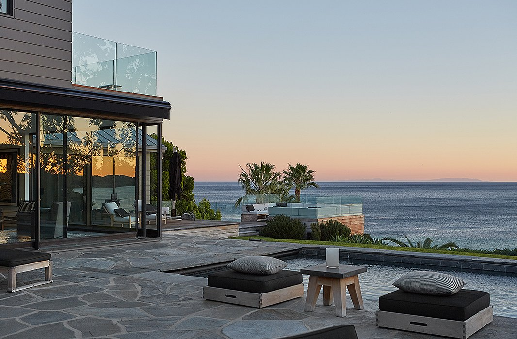 A saltwater swimming pool and a banquette-ringed fire pit overlook the Pacific Ocean.