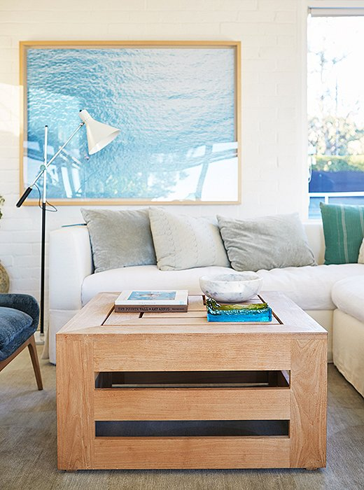 In the tennis house, a watery photograph nods to the Pacific views outside, while a teak coffee table adds natural warmth.