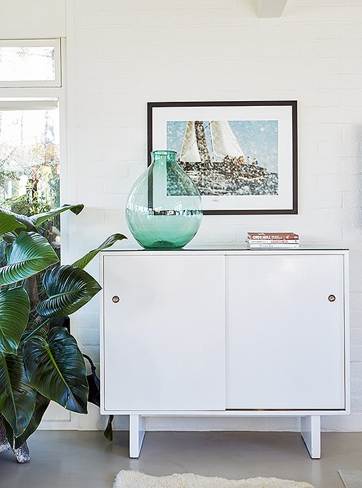 Nautical artwork and a green glass jug play up the beach-house vibe atop a white Widdicomb cabinet.