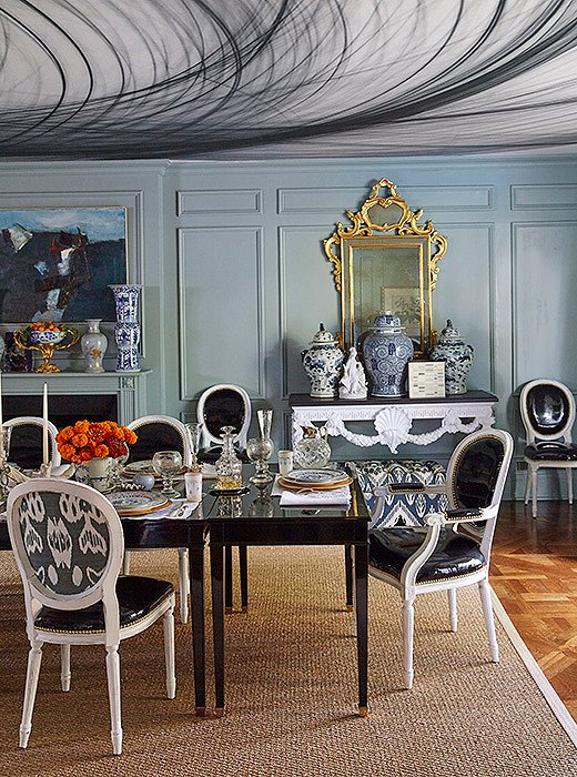 In her Dallas dining room, Michelle upholstered just the backs of her dining chairs in a striking ikat fabric. On the ceiling, patterned wallpaper (actually a detail of a photograph blown up to room size) adds an unexpected moment of drama.