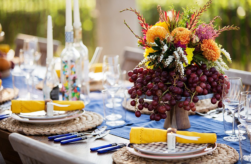 Bunches of grapes arranged on an elevated cake stand form the perfect base for a bunch of golden orange dahlias, mountain snow pierises, and long-stemmed tropical flowers. Photo by Mel Barlow.