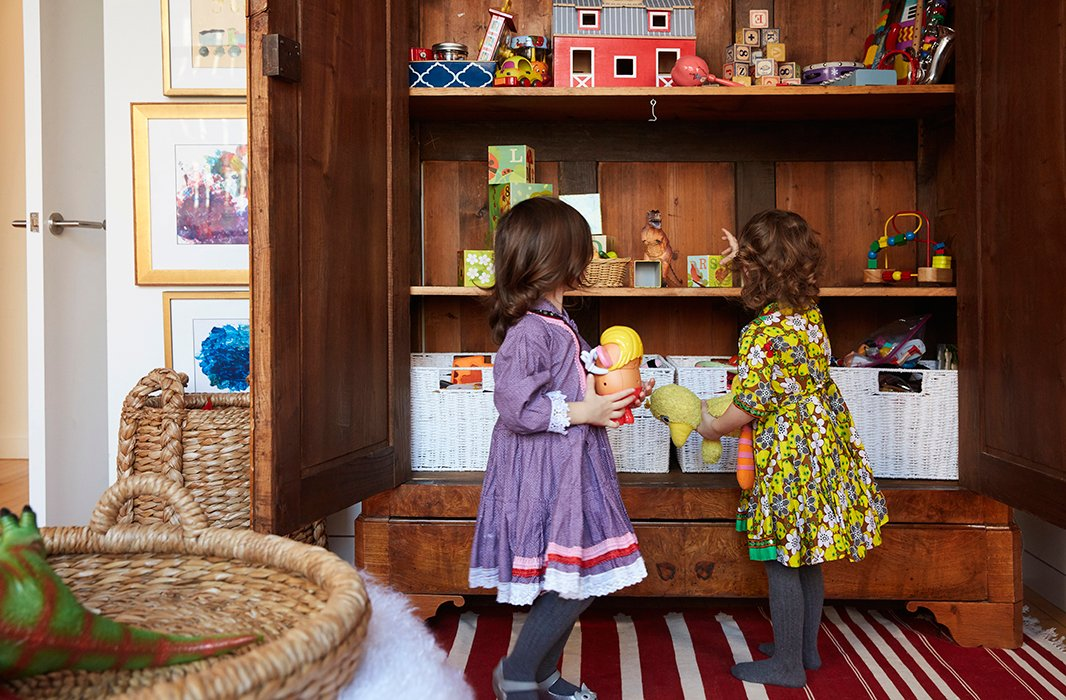 "A row of baskets on the bottom shelf keeps favorite toys at toddler height. And the armoire has been fun for the grown-ups too: ""Rassi and I are both organizing freaks, so it's really nice,"" Zanna says. ""The label-maker came out."""