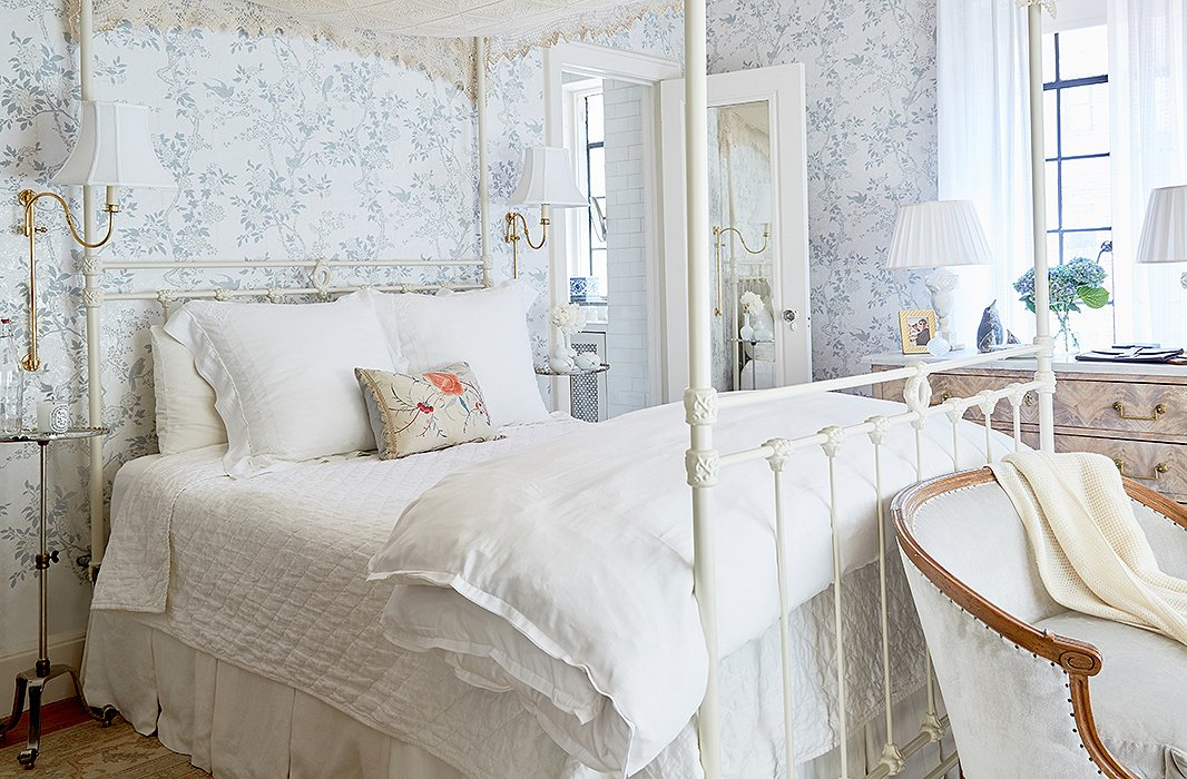 The pale-blue floral wallpaper sets a quiet mood in this cottage-style bedroom. Photo by Tony Vu.