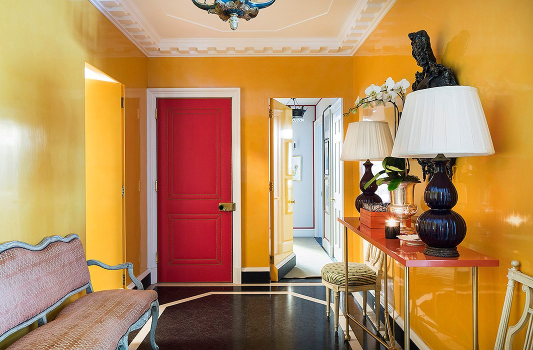 "Kate wanted the windowless foyer to be both warm and inviting. The solution? ""Guts and drama"" by way of lacquered walls (painted in Farrow & Ball's Orangery), stone floors, and an Eve Kaplan mirror. The pièce de résistance is a door upholstered in red Dualoy leather embellished with brass nail heads."