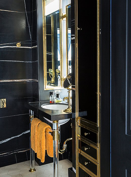 A black marble powder room with brass accents offers a stylish spot to freshen up. A hint of orange, similar in hue to what's seen in the dining room library, appears in a set of hand towels.