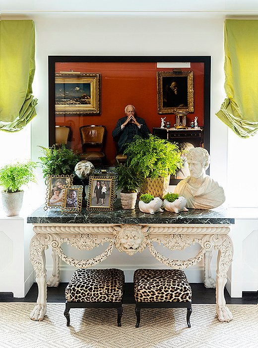 "Bridging the gap between the contemporary and the traditional, a pair of leopard-print ottomans rest beneath a George II marble-top console and a Tina Barney photograph. ""Sometimes people think he's part of the family,"" Kate says with a laugh of the pensive character framed in black, ""and we're okay with that."""