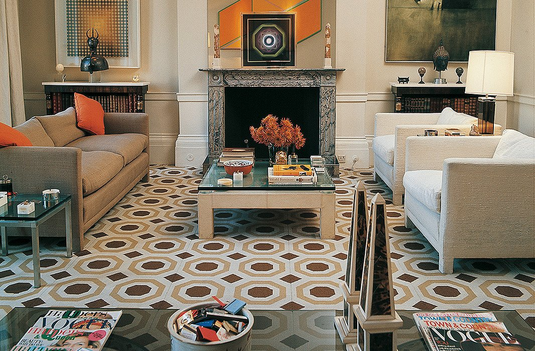 Neutral walls and furnishings create a sophisticated canvas for vivid orange accents and a geometric-patterned carpet. Photo courtesy of Ashley Hicks