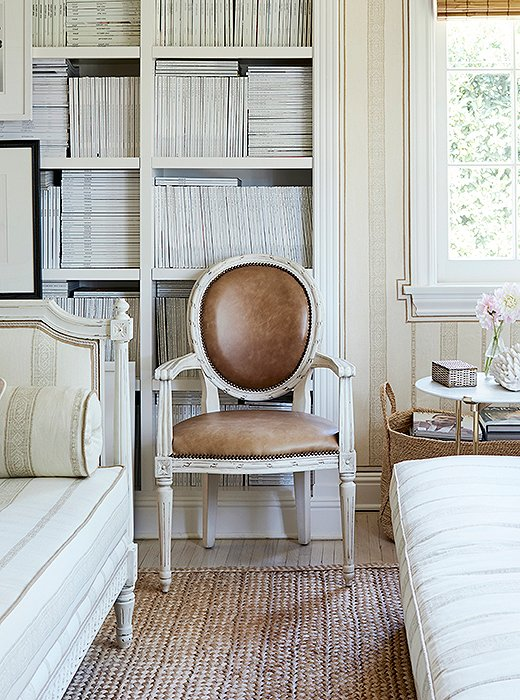 Leather upholstery and a crisp white finish add a modern touch to a round-back Louis XVI armchair. Ribbon-twist carvings encircle the back and the seat. Photo by Joe Schmelzer.