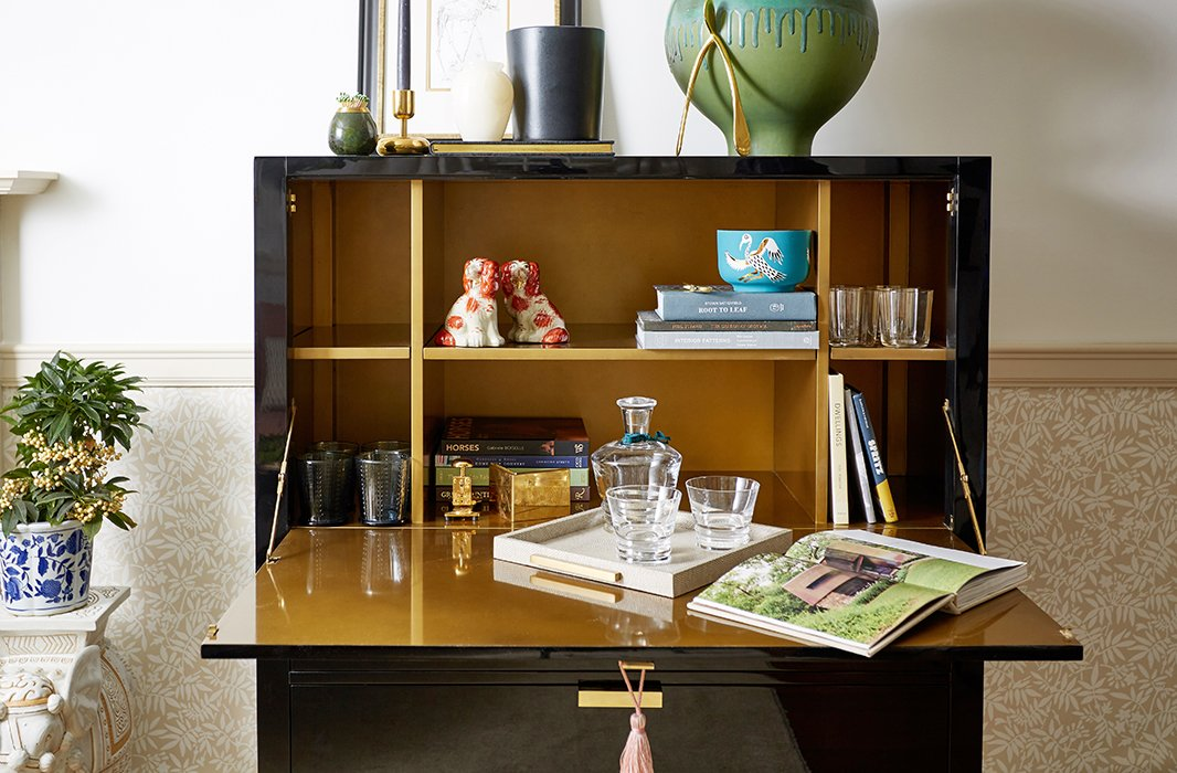 A black lacquered secretary opens to become a surface for work as well as a stylish drinks station ready with barware for cocktail hours on the fly.