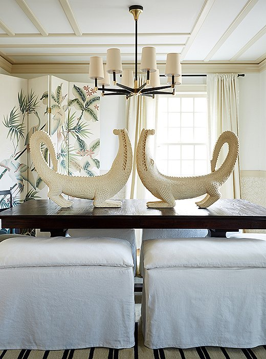 "Oversize cement alligators make for cheeky additions in the dining room and keep watch underneath a chandelier by AERIN. ""You want people to smile when they walk into your home,"" says Debbie, ""and everybody who walks in and sees those alligators think they're totally weird, but they've all smiled… and that's the point."" Just beyond, a vintage screen reiterates the colors used throughout the home."