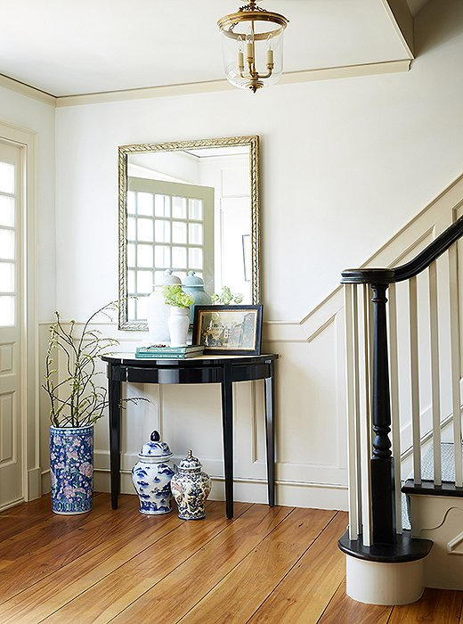 In the foyer, traditional blue-and-white ginger jars and a shapely brass pendant complement a lacquered console by Oomph.