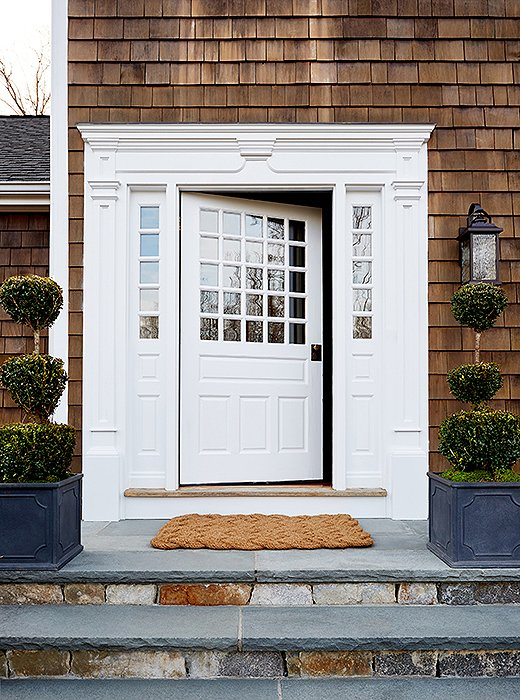 Designed by architect Royal Barry Wills, a specialist in Cape Cod styles, the home features shingled sides and white trim. Topiaries, boxwoods, and slate walkways add to the distinct New England feel.