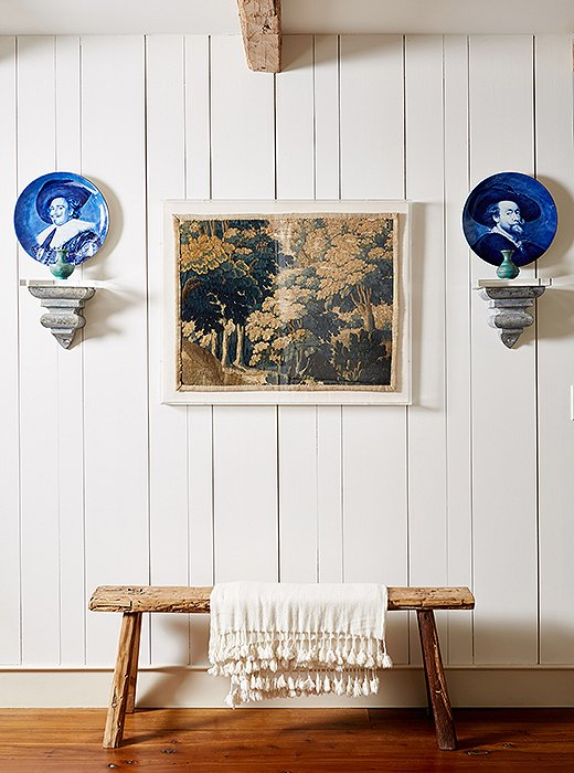 An original piece of Flemish tapestry framed in acrylic, colorful Dutch plates, and a rustic vintage bench play up an old-meets-new mix on the way to the kitchen.
