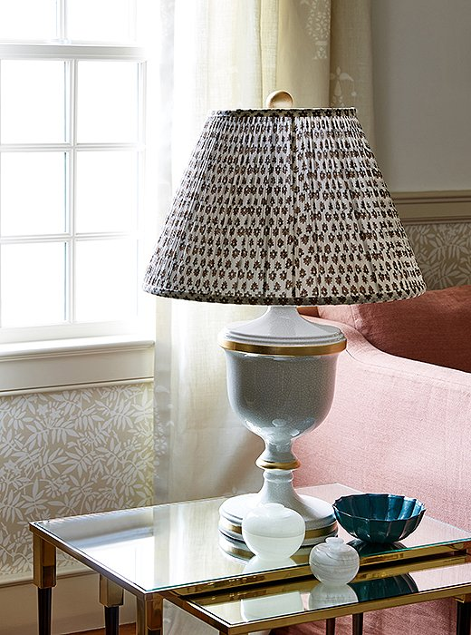 "Vintage lamps topped with shades by Bunny Williams make for elegant accent lighting alongside the sofa. ""A mix of prints keeps the room feeling lively,"" says Nicole. ""They add that token touch of fun."""
