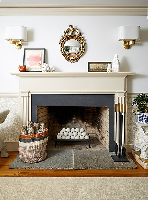 "When it came time to accessorize the fireplace, the focus turned to scale. ""It's quite large,"" says Nicole, ""so a smaller mirror worked best, as we wanted the ceiling to feel higher than it is."" A Federal-style mirror and shaded sconces fit the bill; meanwhile, to transform the fireplace during these warmer months, Debbie opted for decorative spheres. Marble grapes on the mantel tie the whole look together."