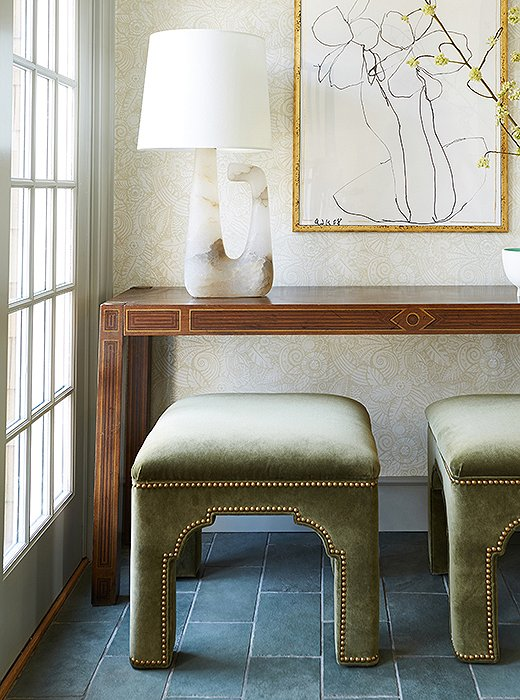 Art by Arthur Krakower, another One Kings Lane favorite, hangs above a vintage console and ottomans by Bunny Williams. The alabaster lamp by AERIN mimics the lines of the sketch behind.