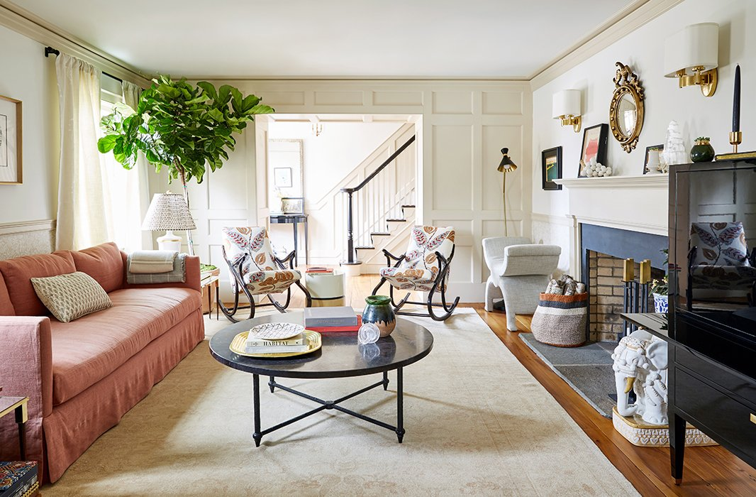 One of the few existing pieces Nicole had to work with was a Belgian linen sofa in dusty pink. She used it to establish the room's color scheme, pulling it through to a Fortuny throw pillow and an Oushak rug. A pair of vintage rockers offset a board-and-batten wall, one of the home's original features.
