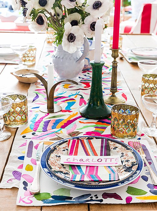 "Kate likes to layer for tea, but she's not one for a tablecloth. Dishes are usually stacked (one vintage, one new) atop place mats—these were inspired by Pierre Frey napkins. The embroidery, found by her mother while traveling in Tulum, guides the eye to ceramics and candlesticks that ""are just as important as the flowers."" Kate purchases colorful beeswax tapers from Paris and eBay packs at a time to coordinate with whatever blooms she has on display."