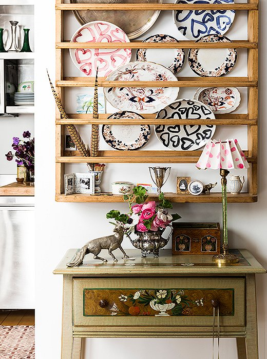 A Scandinavian pine plate rack from Design Works in Cape Cod hangs on a wall adjacent to the dining area—a perfect piece for someone with a penchant for painted plates (the ones with hearts are her own design). Below, a table painted by a family friend hosts a silver fox and an antique vase. The lamp? Vintage, crowned with a shade Kate made with folded paper, velvet ribbon, and Scotch tape.