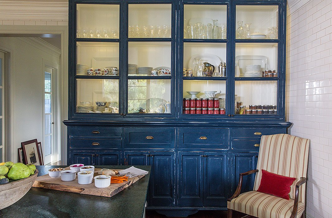 An antique cabinet at Thacher House holds glasses, dishes, and homemade jams.