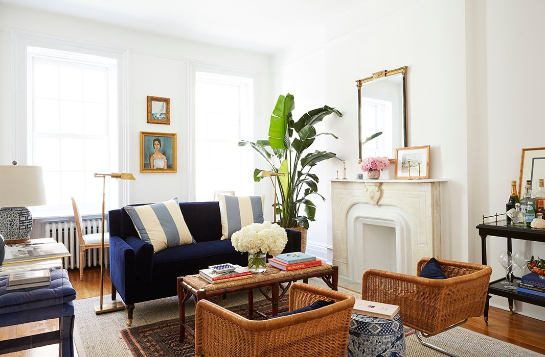 "The starting point for the design was the navy settee. ""I love the classic features of it—the wooden legs and, of course, the color—but the clean lines and the very rectangular angles just felt so fresh,"" Amy says. The walls were painted Benjamin Moore's Chantilly Lace."