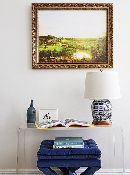 Opposite the fireplace, an acrylic console (one of the few pieces brought from Amy's previous apartment) offers a spot to display favorite photos, books, and objets. A tufted ottoman tucked underneath adds a layered look—and handy seating.