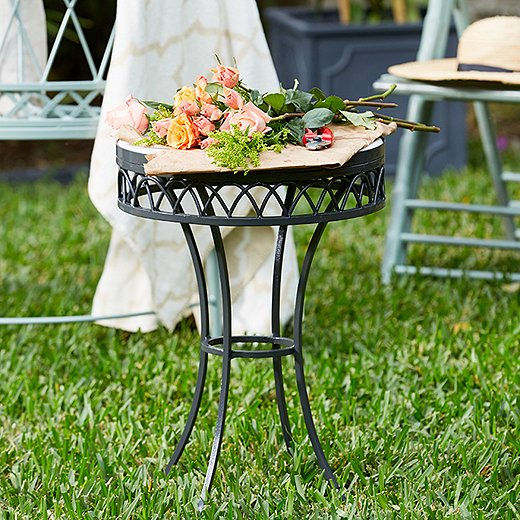 Topped with marble and powder-coated a rich charcoal gray, this wrought-iron accent table is a garden-party standout.