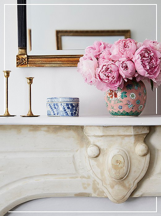 It's all in the mix: Blue-and-white chinoiserie coexists happily with brass and faded gold atop Amy's marble mantel. Photo by Tara Donne.